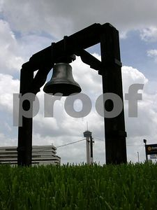 Old bell outside of the Bexar County courthouse with the Tower de Americas in the distance (San Antonio, Texas)