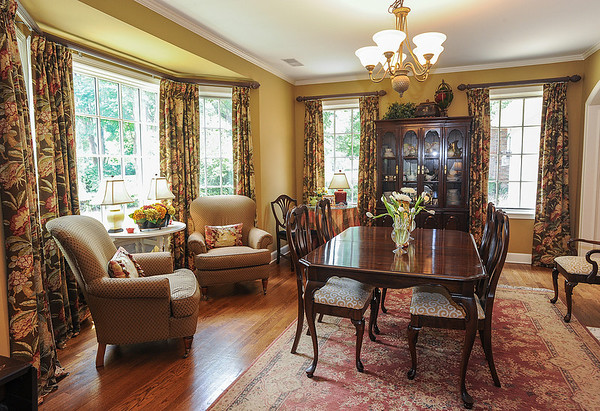 Just off the entry way, the front room of the Patrick family home was transformed into a formal dining and seating area decorated with furnishings and draperies in deep, rich earth tones and lit with plenty of natural light from a series of windows. Photo by Jason R. Terrell