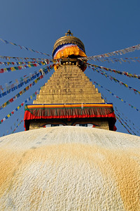 Swayambhunath stupa in Kathmandu, Nepal. A golden spire crowning a conical wooded hill, Swayambhunath Stupa is the most ancient and enigmatic of all the holy shrines in Kathmandu valley. Its lofty white dome and glittering golden spire are visible for many miles and from all sides of the valley. Historical records found on a stone inscription give evidence that the stupa was already an important Buddhist pilgrimage destination by the 5th century AD.