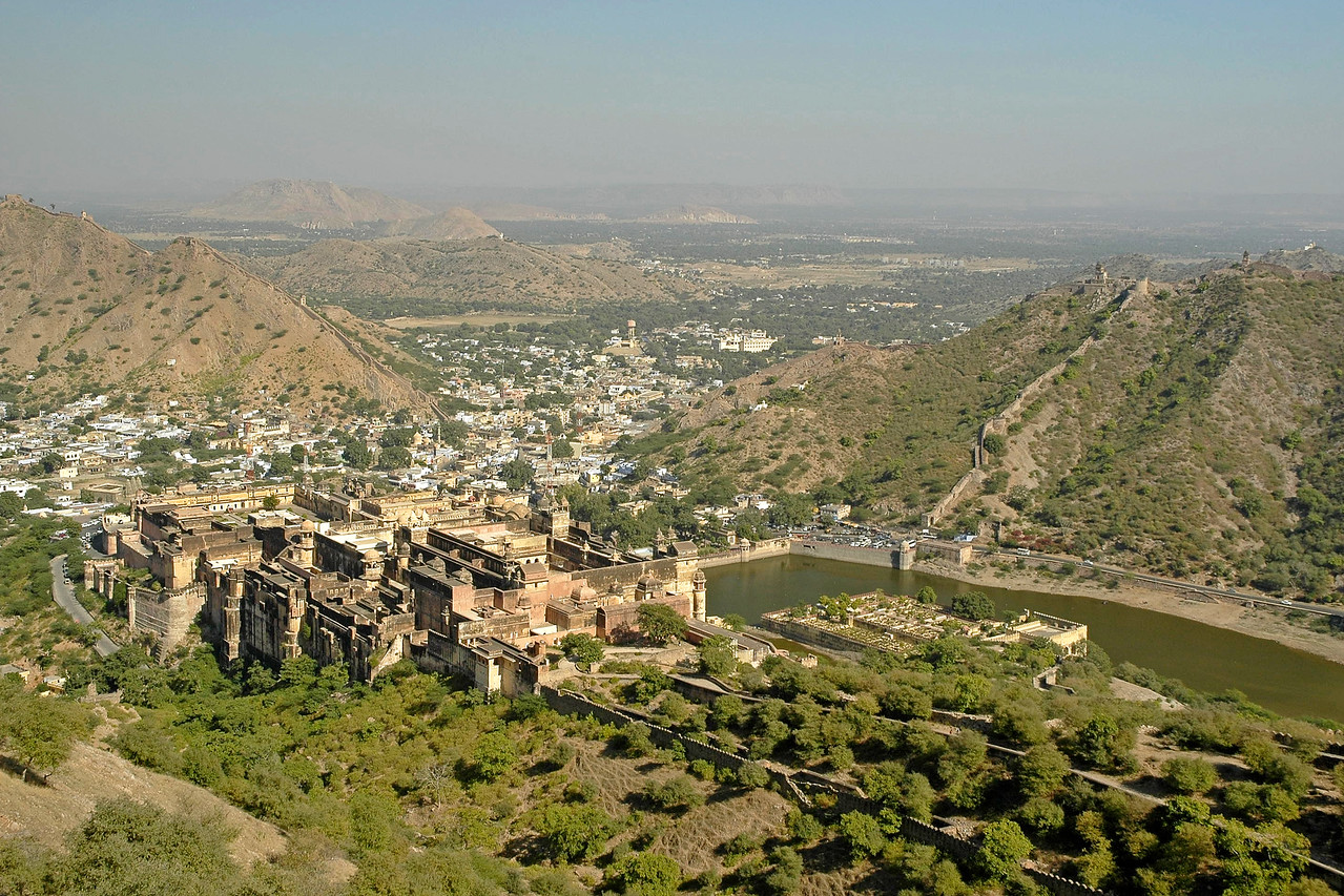 View from Amber Fort which is located in Amber (Jaipur). Amber used to be the capital of the Kachhwaha clan, till Jaipur was made the official capital in 1727. The Amber Fort looks stunning, all-built in white marble and red sandstone. To add to its charm, Maotha Lake makes its foreground. The crystal mirror image of the Fort, on the still waters of the lake, seems to be a beautiful illusion. Amber Fort is usually pronounced as Amer Fort. In 1592, construction of the Fort was started by Raja Man Singh I. However, the Amber Fort took its present form during the reign of Raja Jai Singh I. <br /> <br /> The outer appearance of the Fort, being rough and craggy is totally different from its core. The interior of the Fort provides a soothing and warm ambience, which is least expected from its outer appearance. The marvelous decoration of the Amer Fort is influenced by both, the Hindu and Muslim manner of ornamentation. Exquisite paintings of hunting scenes on the walls depict the temperament of the Rajputs.