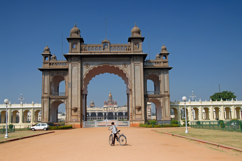 Boy on a cylce in front of the Palace of Mysore (Amba Vilas) which is situated in the city of Mysore, Karnataka, Southern India. It was the official residence of the former royal family of Mysore, and also housed the durbar (ceremonial meeting hall of the royal court).<br /> <br /> The palace was commissioned in 1897, and its construction was completed in 1912. The Wodeyar Mahararaja's of the Mysore state used to reside in this. The original palace built of wood, got burnt down in 1897 and was rebuilt for the twenty fourth Wodeyar Raja in 1912. Designed in Indo-Saracenic style by the well-known British architect, Henry Irwin, the palace is a treasure house of exquisite carvings and works of art from all over the world.