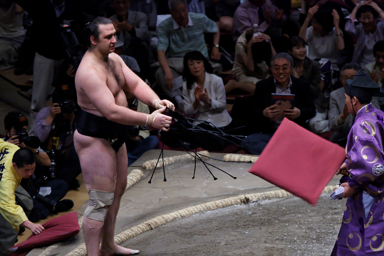 Win - Kotooshu just won over Yokozuna Asashoryu and everyone is throwing cushions... Sumo Tokyo tournament. May 2008.  This tournament was won for the first time ever by a european sumotori, the bulgarian born Kotooshu.