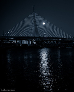 Zakim Bridge Cold Moon.  The January 2010 full moon passes through the cable stays of the bridge.  I like the reflection of the moon light on the water.