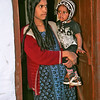 Toda village, woman and child in doorway of home