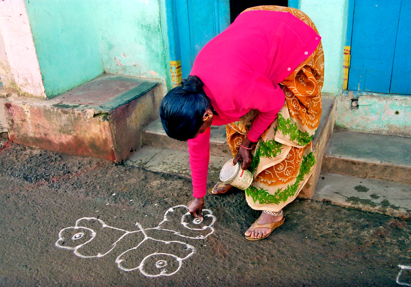 Ooty, woman drawing welcome symbol with rice powder