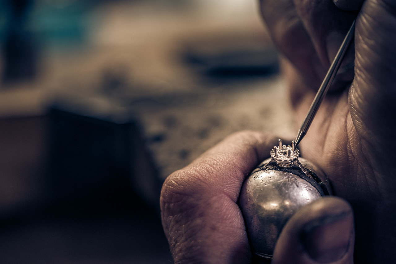 A working man assembling a handmade ring.