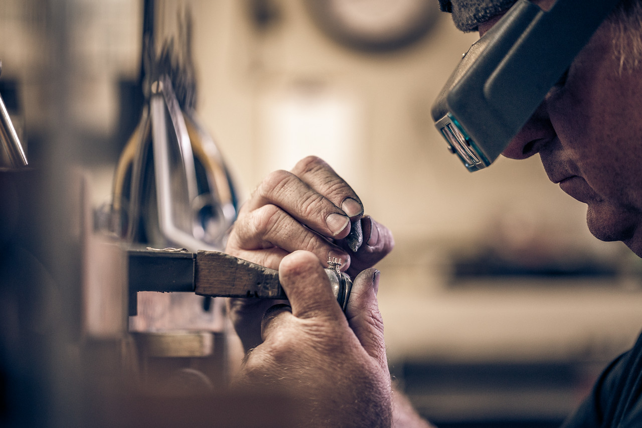 An older man crafting a ring.