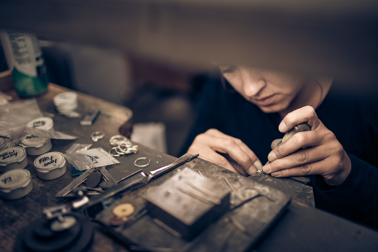 Portrait of a woman working on rings.