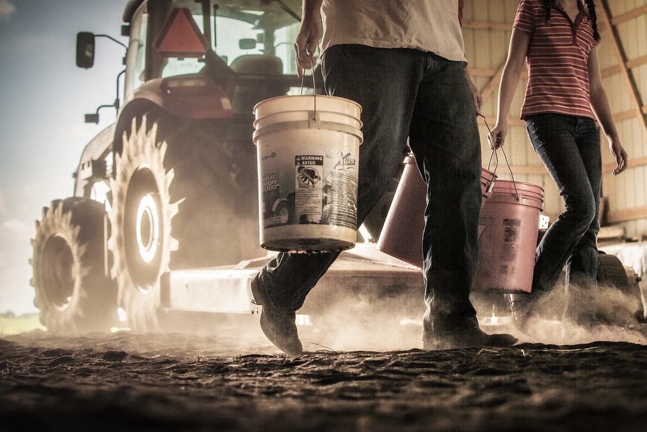 Father and daughter carrying buckets on the farm.