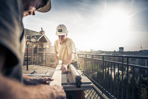 Two men working outside on a table saw