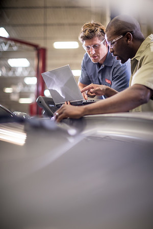 Two working men at an Auto shop.