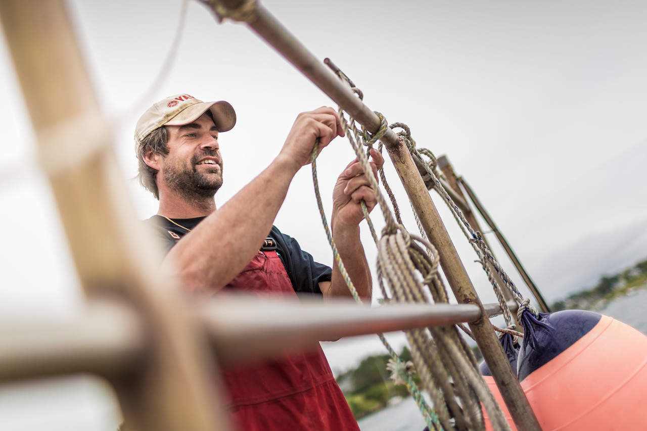 A man on a boat tying rope.
