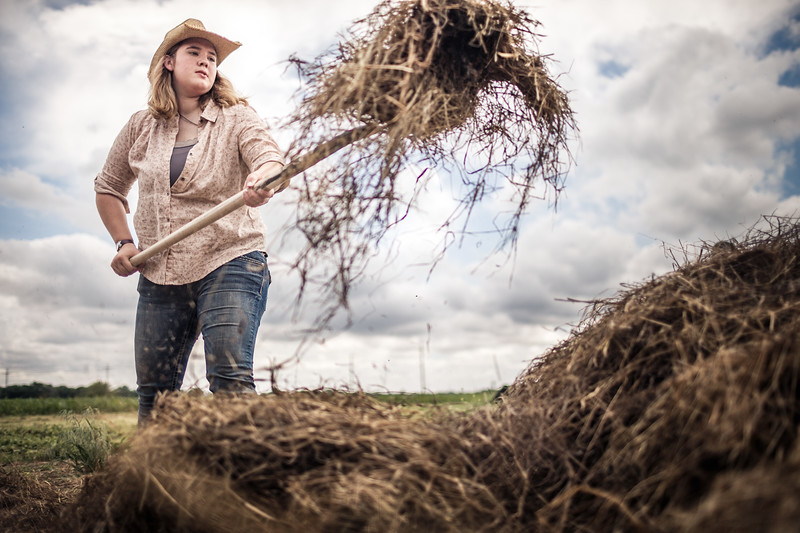 Woman farmer moving hay