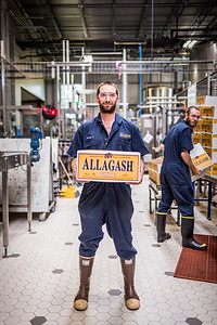 Two working man at a brewery holding a large case of beer