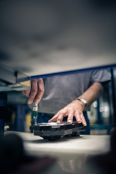 A man at work using his hands to screw metal parts together.
