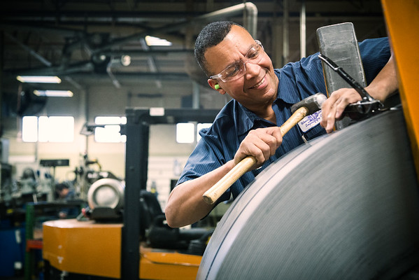 A man using his hands to measure a roll of steel.