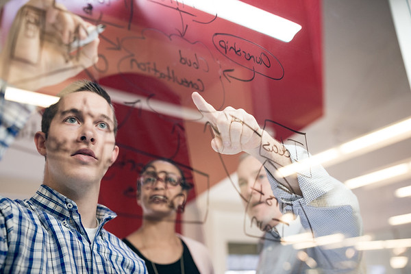 Team of creatives illustrating diagrams on glass.