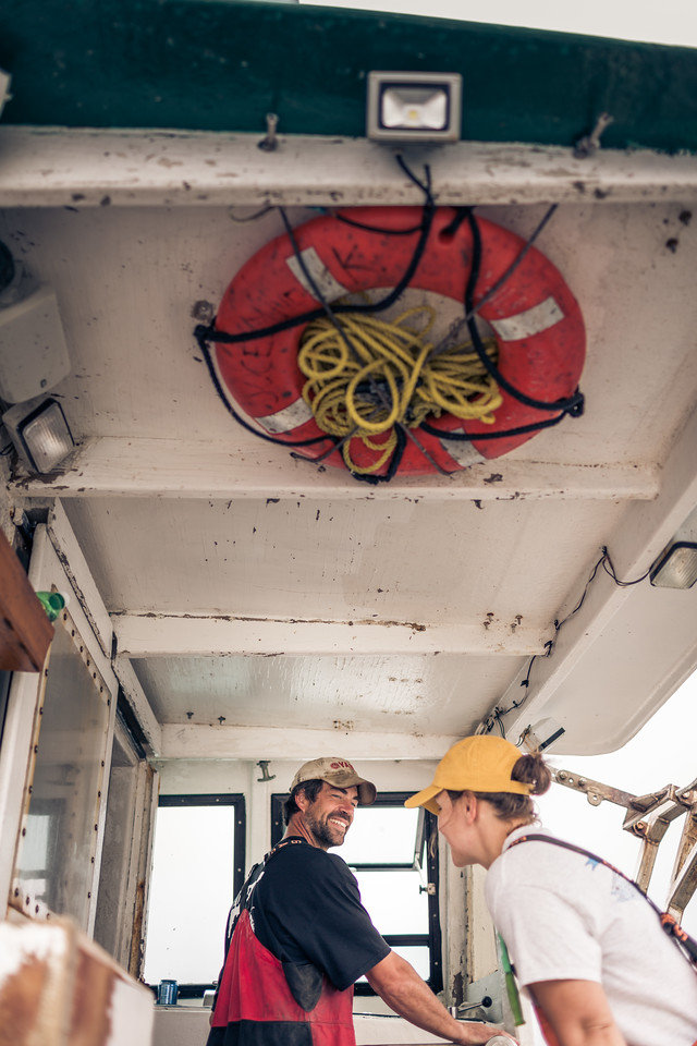 Two workers on a marina lobster boat.