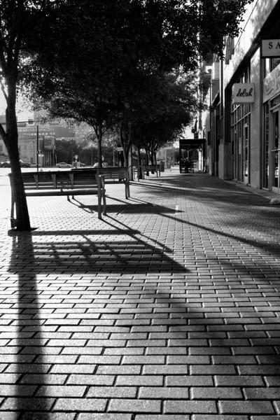 Morning light shadows bench downtown.