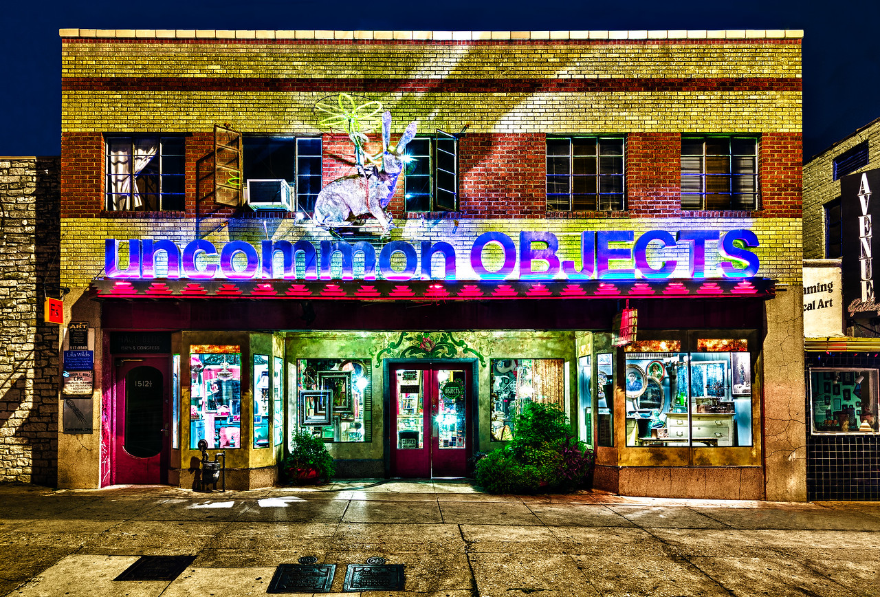 """Uncommon Objects is a collection of booths that sell vintage and eclectic art in the South Congress area known as SoCo in Austin Texas. The proprietor Steve Wiman describes Uncommon as """"Raw materials for creative living."""" It is located about a mile south of Riverside drive in the heart of SoCo. There are many shops and places to grab a bite to eat nearby including a trailer park of different cuisines, Guero's Taco Bar and Homeslice Pizza to name a few. This shot was taken late Sunday night since that is the only time that cars are not parked in front of all the shops."""