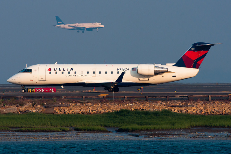 While this Delta Connection CRJ is getting ready to depart, a JetBlue A320 is arriving in the distance.
