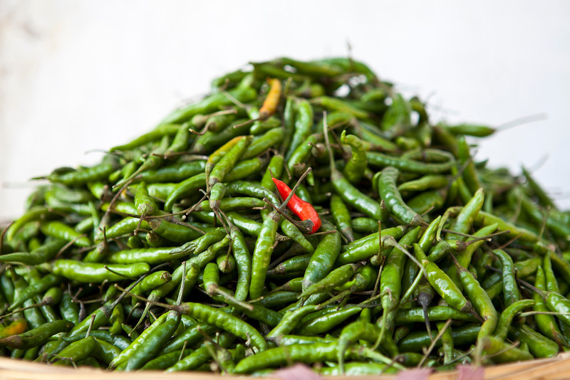 EAST BHUTAN. A BASKET FULL WITH GREEN PEPPERS AND ONE RED PEPPER. [3]