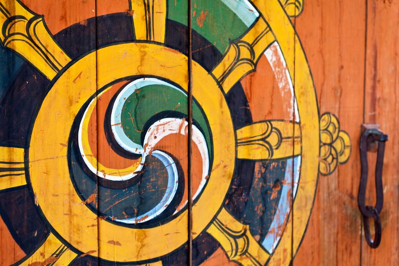 LUENTSHE DZONG. DOOR WITH DHARMA WHEEL (WHEEL OF LIFE).