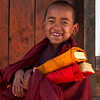 DRAMETSE GOEMBA MONASTERY WITH MONKS SCHOOL. EAST BHUTAN. LITTLE MONK WITH HIS BOOKS.
