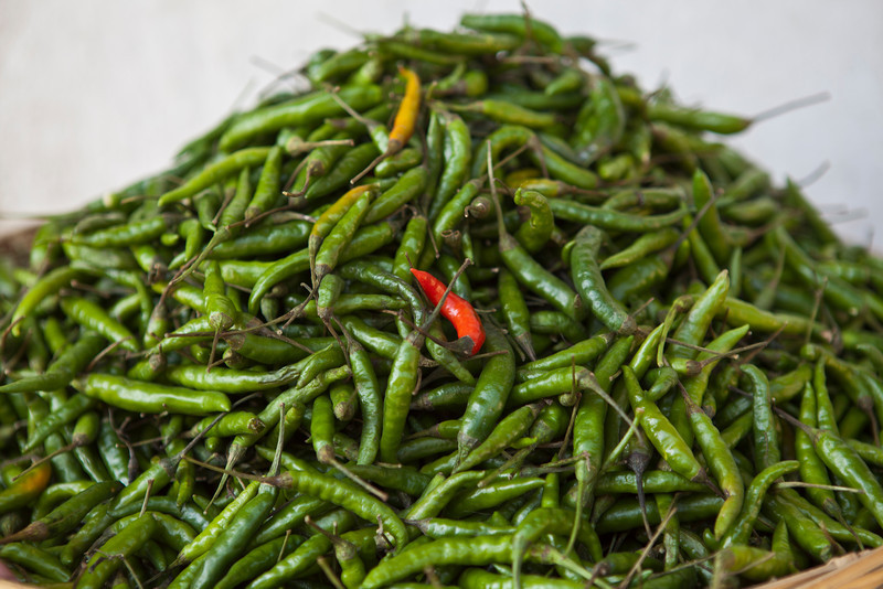 EAST BHUTAN. A BASKET FULL WITH GREEN PEPPERS AND ONE RED PEPPER.  [2]