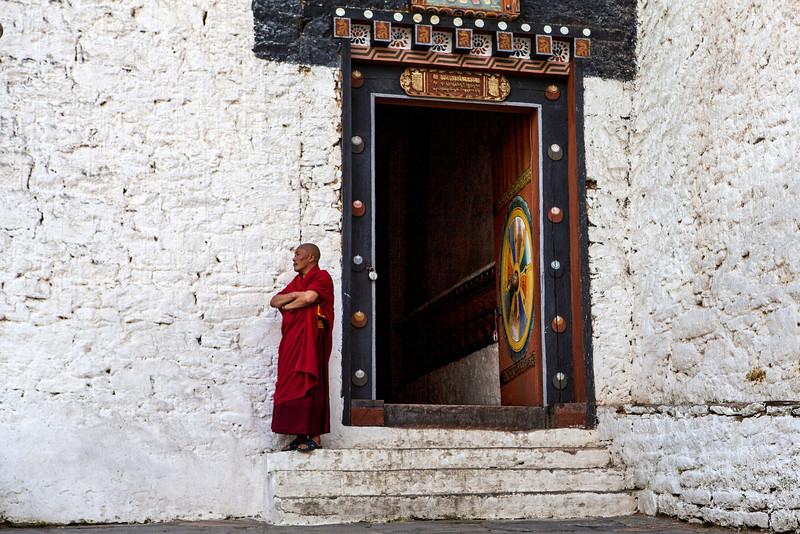 TRONGSA DZONG. MONK WAITING AT THE ENTRANCE GATE.
