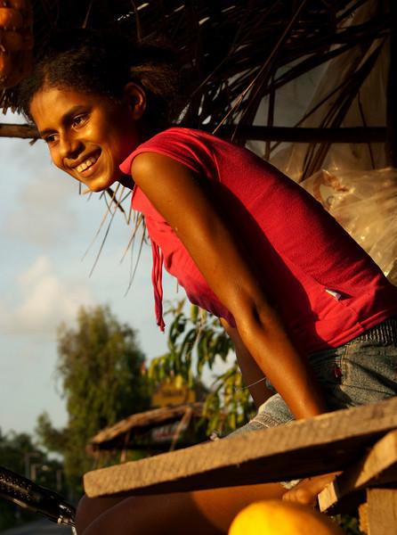 FRUIT SELLER GIRL AT SUNSET. MACEIO.  BARRA DE SAO MIGUEL. ALAGOAS. BRASIL.