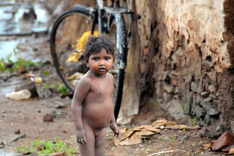 Little naked girl outside her simple home. Very basic rural living conditions in this maharashtrian village enroute to Chinmaya Vibhooti, Kolwan, Maharashtra (MH), India