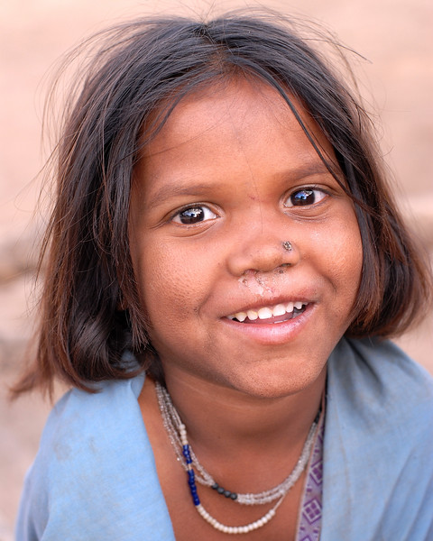 This sweet child was amused at her photo being taken. The whole village in which she lives BPL (Below the Povery Line) and lead a simple but difficult life. Rural Maharashtra. Shot in a village near Nagpur, Maharashtra. India. South Asia.