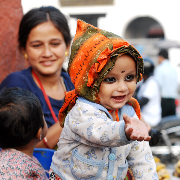 Reaching Out - child with kajal in eyes with a dotting Nepalese mother in the back. Patan Square, Kathmandu, Nepal.
