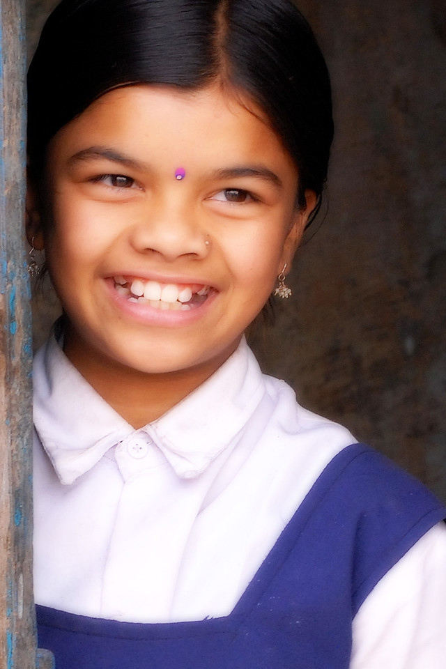 School girl in uniform with a big smile peeping from behind a door. Village near Nagpur, Maharashtra, MH, India