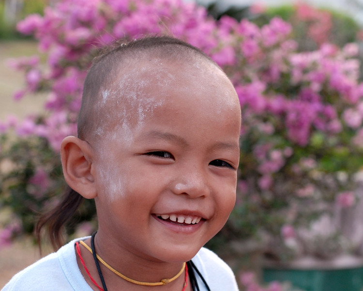 Little boy in Thailand. Shaved head and very playful this child was playing near a temple in Bangkok, Thailand. South East Asia.