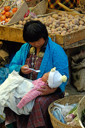 A Bhutanese mother feeding her child. At the Thimphu Sunday market whole familes come and sell/shop at the venue.