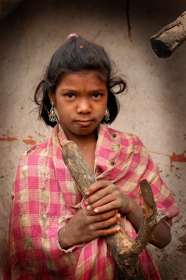 Spotted this girl standing near her house next to a tree stub. The whole village lives BPL (Below the Povery Line) and lead a simple but difficult life. Rural Maharashtra. Shot in a village near Nagpur, Maharashtra. India. South Asia.