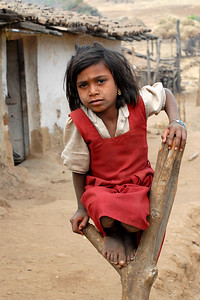 Spotted this girl in school uniform sitting outside her house on a tree stub. The whole village lives BPL (Below the Povery Line) and lead a simple but difficult life. Rural Maharashtra. Shot in a village near Nagpur, Maharashtra. India. South Asia.