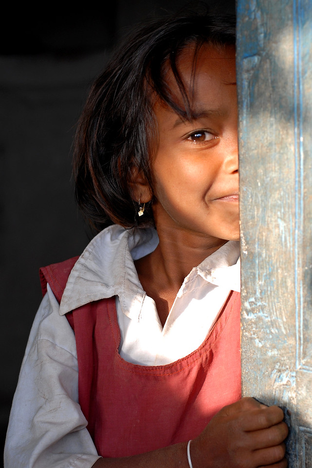 Saw this girl in her school uniform standing at the door - hiding but wanting to be seen. Smiling but shy. Rural Maharashtra. Shot in a village near Nagpur, Maharashtra. India. South Asia.
