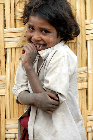 Spotted this girl standing close to me but a bit shy. Even with her folded hand pose it was clear that she was just being shy and she broke into a smile. Shot in a village near Nagpur, Maharashtra. India. South Asia.