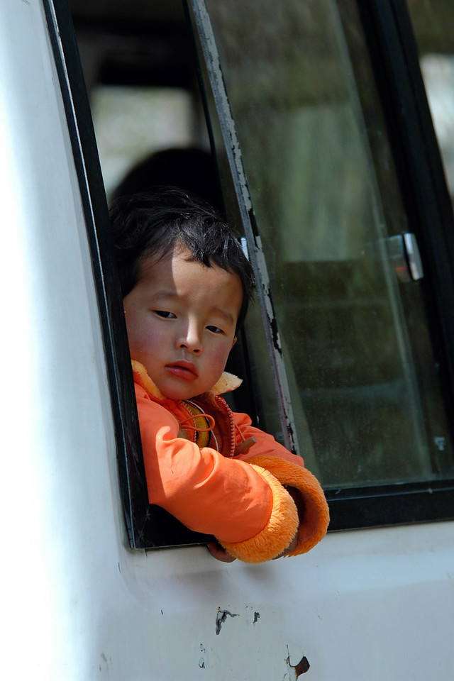 Small Bhutanese boy looking out of the window of a bus.