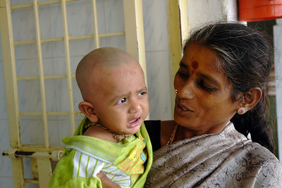 Mundan (head shaving) is done for small children as a tradition and also as an offering to the God. Young baby crying in the mother's arms after the shaving is done in Tirupathi, Andra Pradesh, AP, India