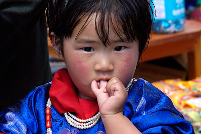 Young buddhist visiting the Paro Tsechu Festival with Dad at Paro, Bhutan. The land of the Dragon