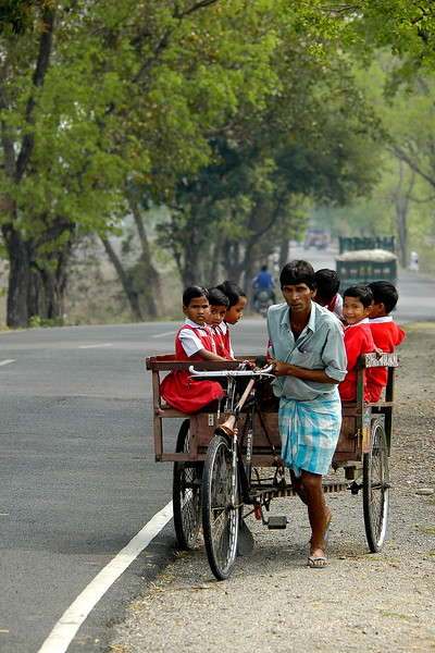 Cycle rickshaw puller carrying children to school. Border of India and Bhutan.