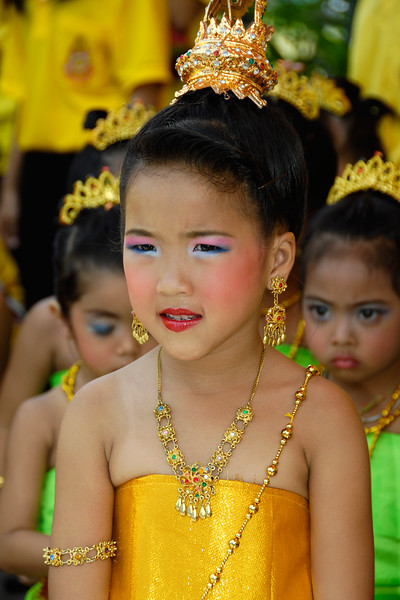 Little girls all dressed up in traditional silk dresses and bright colours as they get ready for practise in Bangkok, Thailand.