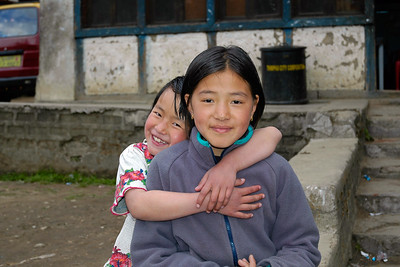 Two loving children sitting outside their home in Thimphu, Bhutan.