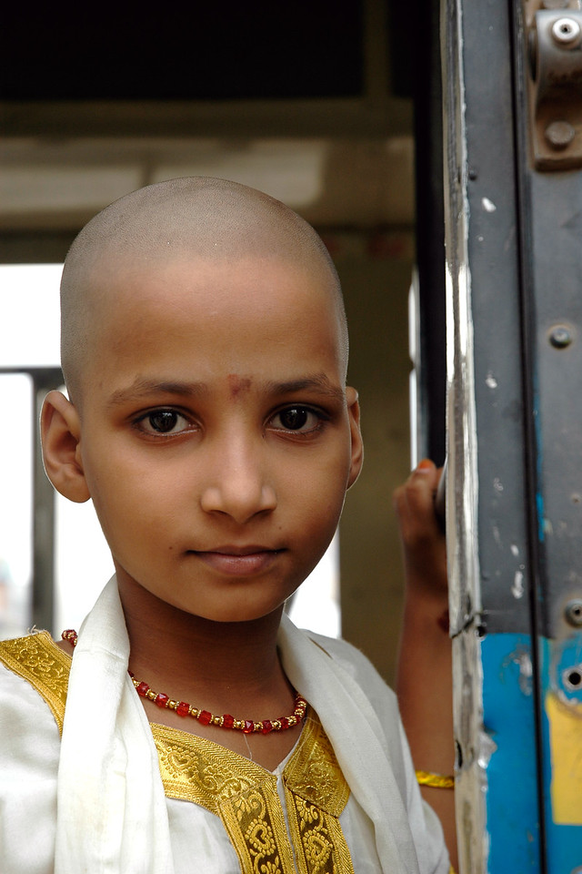 Little girl returning in the state transport bus after the mundan (head shaving) which is done for small children as a tradition and also as an offering to the God. Young and old get their heads shaved in Tirupathi, Andra Pradesh, AP, India.