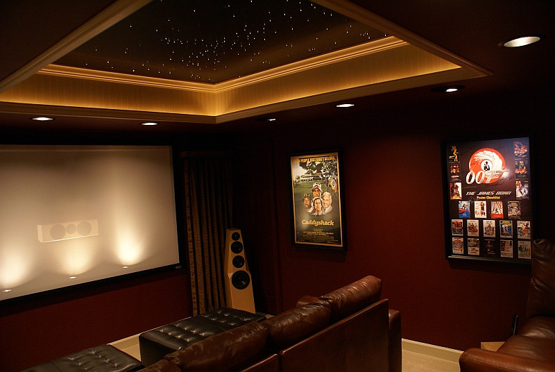 Theatre design and AV installs by 360 Home Cinema<br /> <br /> Twinkling starlight LED and rope lighted tray ceiling.<br /> Backlit screen with recessed speaker for added interest.<br /> Projection cans illuminate framed posters with zero spillover onto wall surfaces.<br /> All lighting is tied into a programmable controller allowing for multiple settings.