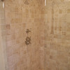 Price Masterbath shower: Natural stone with frameless enclosure.
